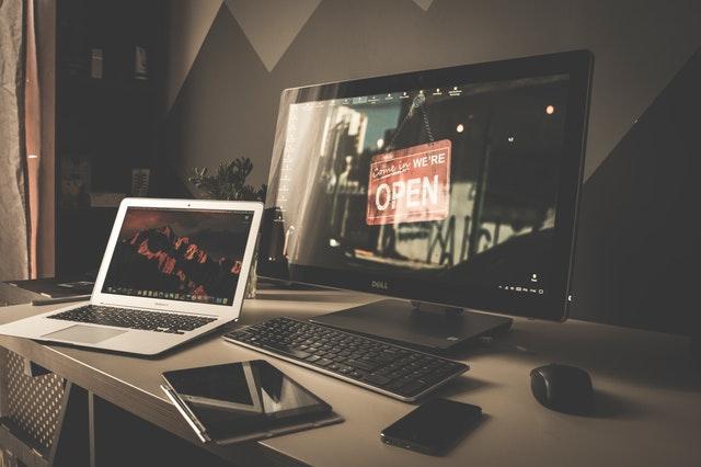 Menší biely notebook a vedľa väčší čierny počítačový monitor, nápis OPEN